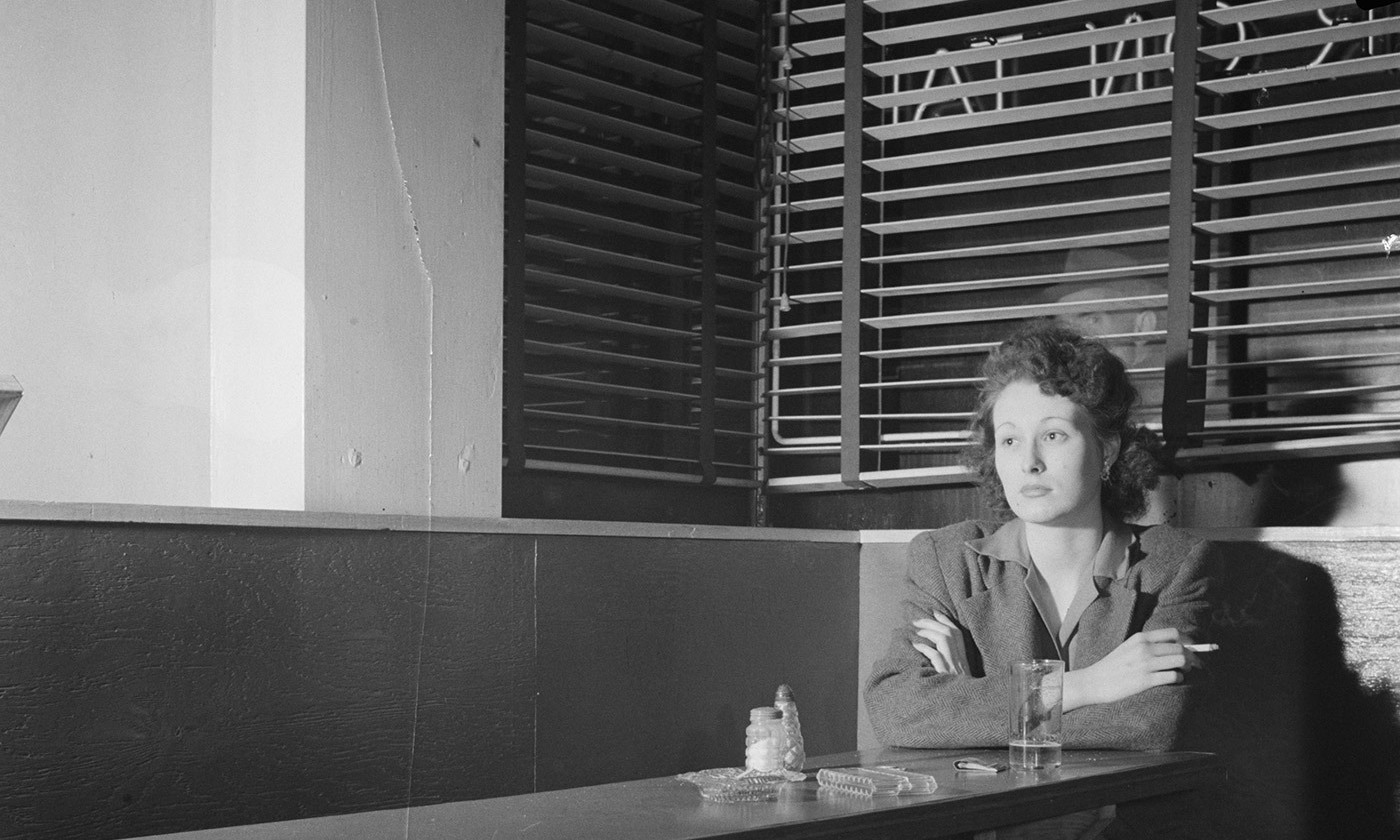 <p>Girl sitting alone in the Sea Grill, a bar and restaurant in Washington, DC, 1943. <em>Photo by Esther Bubley/Library of Congress</em></p>