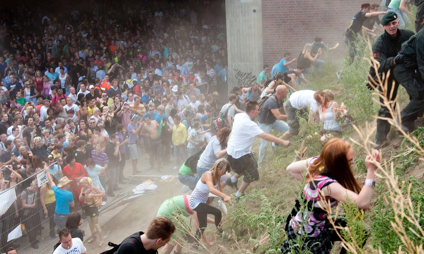 <p>Revellers rush up a hill after panic broke out during the Love Parade in Duisburg, Germany, on 24 July 2010. <em>Photo by Erik Wifferes/Afp/Getty</em></p>