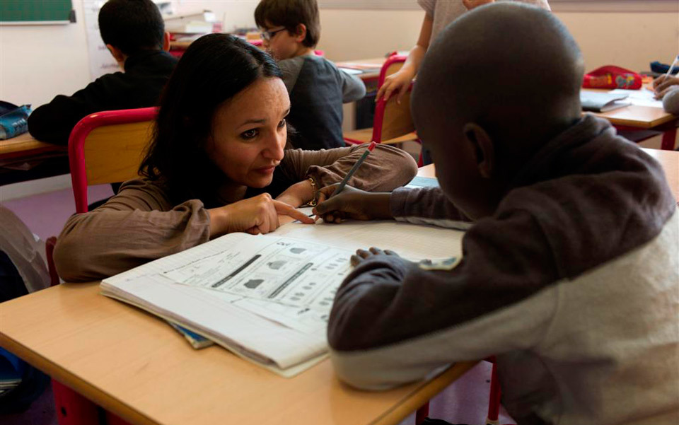 Photograph of a teacher talking to a child